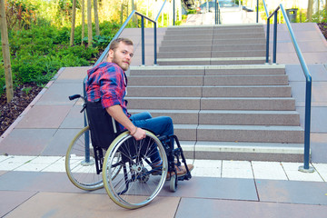 disabled man in wheelchair in front of stairs