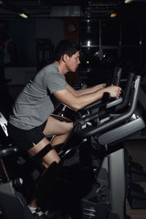 Side view portrait of a man workout on a fitness machine at gym.