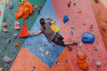Young man professional climber exercising at indoor bouldering artificial wall