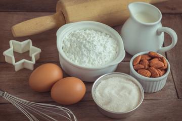 Baking ingredients flour, egg, milk, almonds, sugar on wooden table