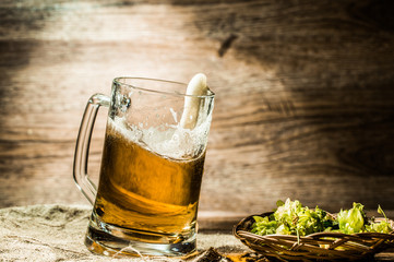 Beer in tankard close-up stands on linen cloth