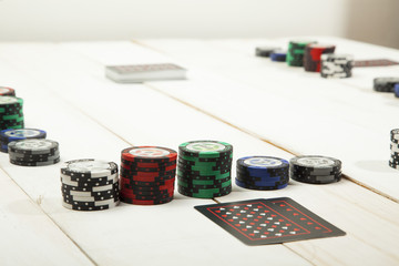 Game of poker chips and cards black on white wooden table