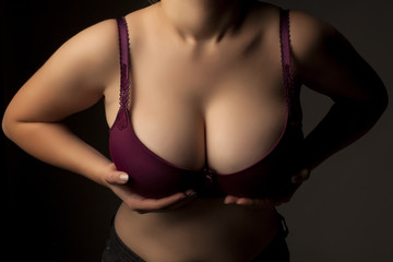 Large and beautiful women breasts in purple bra