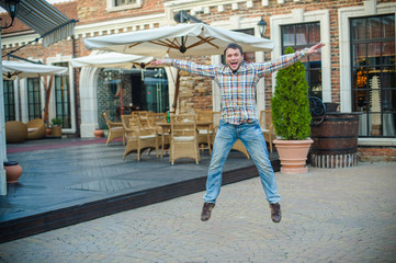 happy man jumping from joy in the city near a street cafe