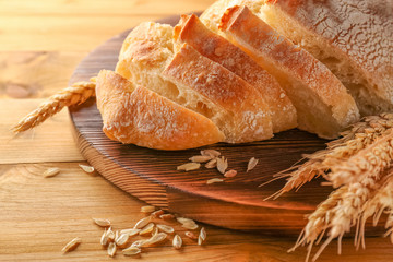 Sliced fresh bread with wheat spikes on wooden cutting board closeup