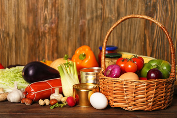 Variety of food products in basket on wooden background