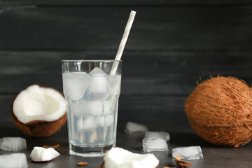Glass of coconut water and fresh nut on dark wooden background