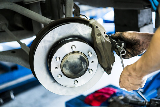 Car disc brake in process of assembly and repair caliper maintenance by mechanic hand.