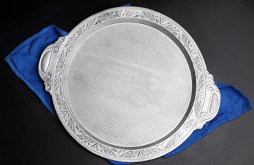 Silver tray.With blue closth .On dark stone background