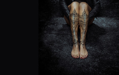 Closeup woman legs with henna tattoo over black stone floor