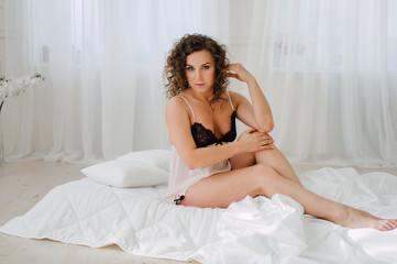 Sexy woman in bed in the morning showing her beautiful body. She doesn't wants to wake up. Awaken with natural light in her bedroom and covered with the bed sheets.