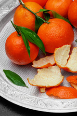 Fresh tangerine clementine with leaves in silver tray.closeup.Selective focus