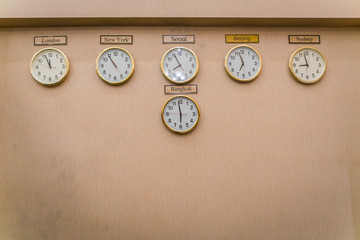 Clocks shows different time zones on old wall .