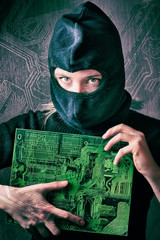 hacker girl in balaclava holding motherboard on a background silhouette drawing circuit board. concept of computer hacking threats.