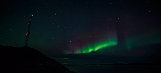 Radio tower on the hill and northern lights over the fjord in th