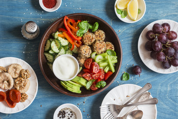 Vegetarian snack table - quinoa meatballs, fresh raw vegetables, grapes, dried fruits on wooden table, top view. Flat lay