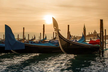 gondola boats stand at pier in Venice