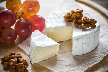 Camembert cheese with walnuts and grape