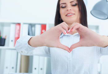Young female office worker show heart hands. We love our customers!