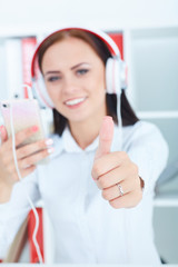 Beautiful girl  in headphones listening to music from smartphone in office.