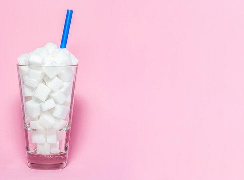 Glas voll mit Würfelzucker - Symbol für Zucker als versteckter Krankmacher.