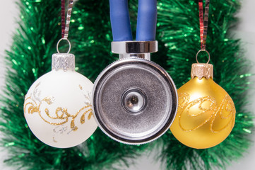 Medical Christmas and New Year. Stethoscope surrounded by white and gold christmas tree balls with blurred christmas decoration on background - green garlands. Concept for the New Year in medicine