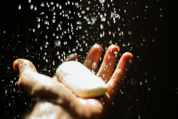 Open human hand with soap under water drops