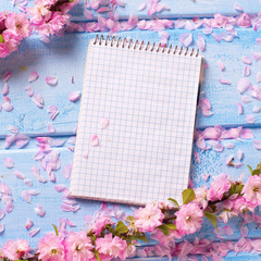 Background  with sakura  pink flowers and empty tag  on blue woo