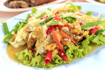 Thai Food, Spicy salad with fried eggs with soft-focus in the background. over light