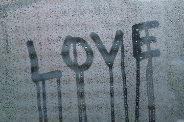 Texture water droplets on window glass with love text