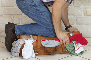 Mann drückt vollen Koffer mit Knien fest