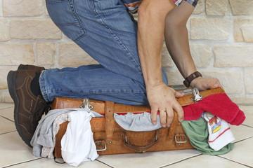 Reisender quetscht alten vollen Koffer mit Knien