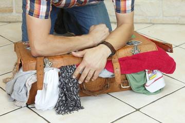 mann quetscht Koffer zusammen, zu voll