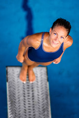 Wall Mural - Portrait of female diver. Female diver standing on the jumping board.