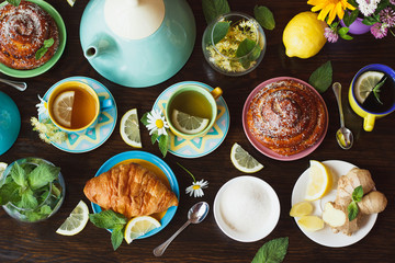 Cups with green tea, lemon and baked goods on the wooden background