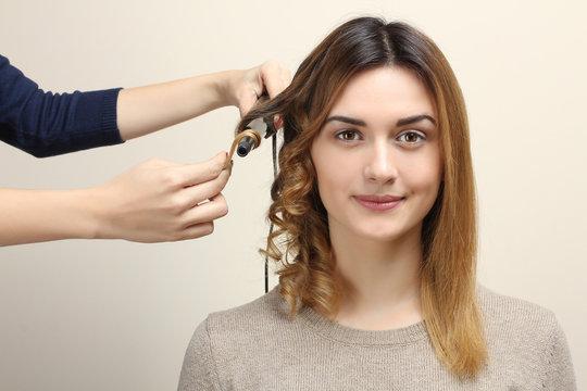 Hairdresser turns girl's hair on curling.