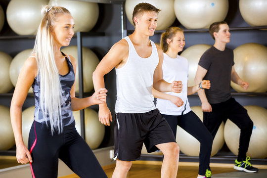 Motivated workout group jumps at platforms in a fitness gym
