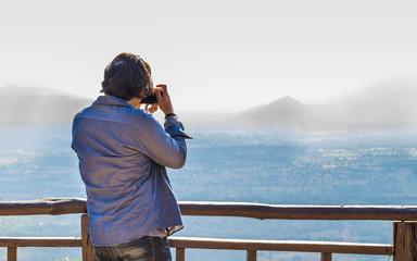 a man is taking a landscape photo.