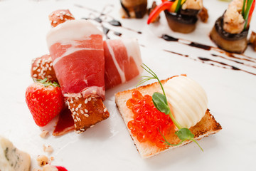 Bacon rolls with caviar toasts close-up. Tasty appetizers on white plate, delicatessen mix. Luxury lifestyle, expensive food, restaurant menu, gourmet concept