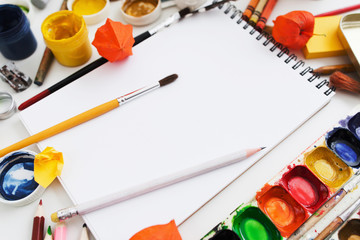 Drawing supplies close-up, mockup. Blank sketchbook with watercolor palette, pencil, paintbrush and other stuff. Art, painting, drawing, inspiration, creativity concept