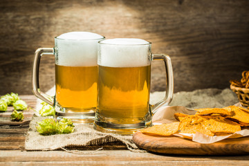 Couple beer mug with hop and chips on boards at linen cloth