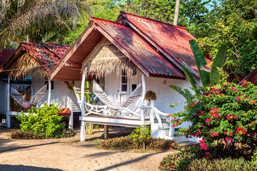Small white bungalows with hammocks on the terrace in the tropic