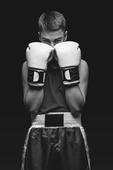 Young boxer sportsman on black background