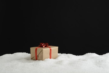 Caja de regalos en la nieve sobre fondo negro