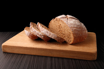 bread, cut on an oak board/ bread, cut on an oak board on a dark background