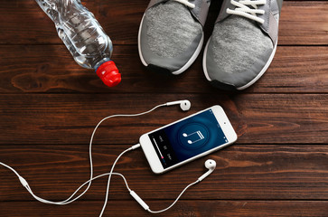 Sport shoes and cellphone on wooden background