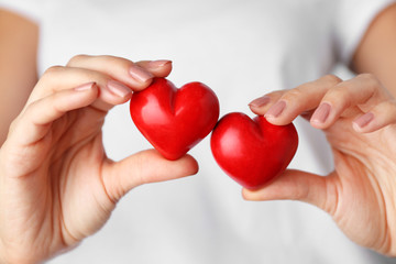 Woman holding red hearts in hands, closeup