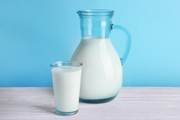 Milk in glass and jug on white wooden table, closeup
