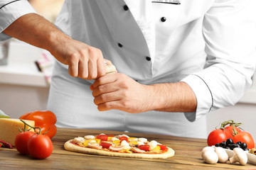 Male hands preparing pizza at wooden table closeup