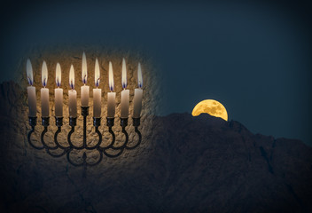 Low key composite image with menorah with glitter lights of burning candles and rise of moon above mountains